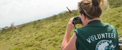 Voluntaria observando jirafas como parte de su voluntariado de conservación en Kenia.